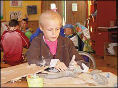 A child working with clay in the arts and crafts room at Paul Newman's Hole in the Wall Camp.