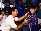 Steve Garvey helps a child batter up at the All Star Carnival